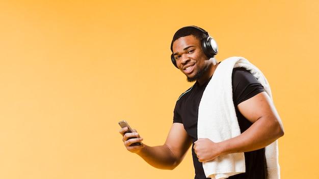 Smartphone atletico della tenuta dell'uomo di smiley