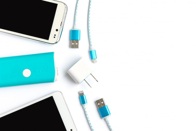 Smartphone bianco con batteria banca e cavi di ricarica usb in vista dall'alto