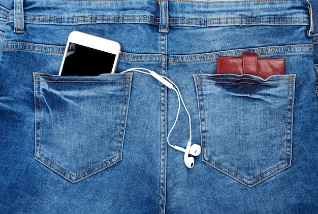 Smartphone bianco con le cuffie nella tasca posteriore delle blue jeans