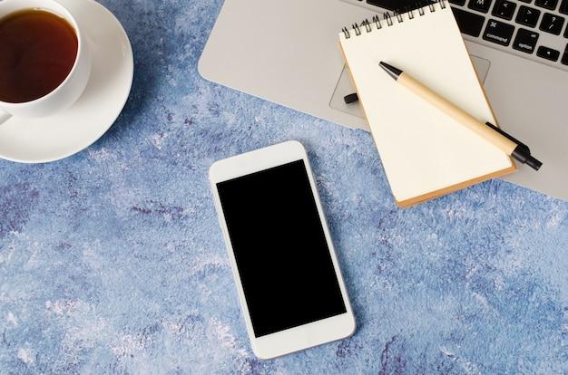Smartphone bianco con lo schermo in bianco nero sulla scrivania con il computer portatile, il taccuino vuoto e la tazza di tè. mock up del telefono.