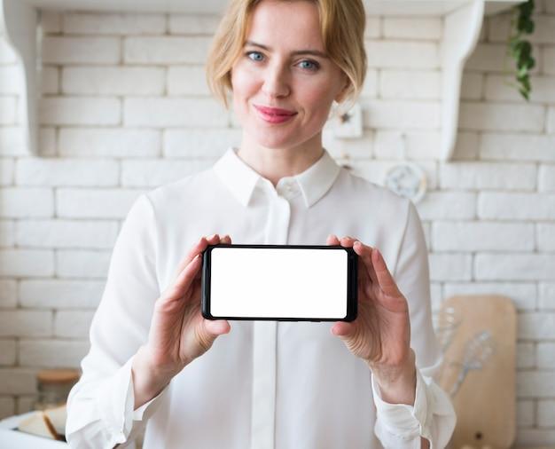 Smartphone biondo della tenuta della donna di affari con lo schermo in bianco