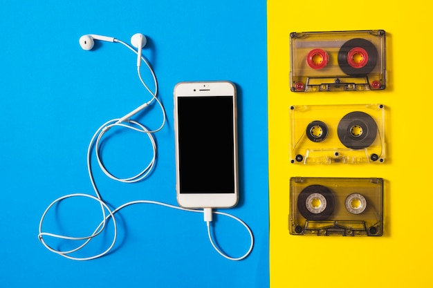 Smartphone collegato con auricolari e cassette su doppio fondo