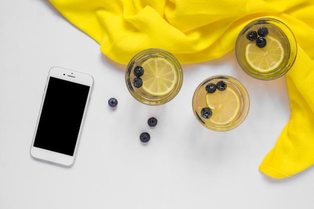 Smartphone con bicchieri di succo di limone e tessuto giallo su sfondo bianco