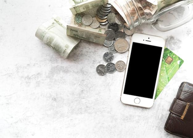 Smartphone con denaro, carta di credito e portafoglio