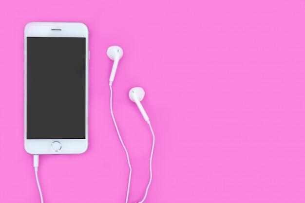 Smartphone con le cuffie sul rosa con lo spazio della copia e il percorso di ritaglio. disteso. vista dall'alto.