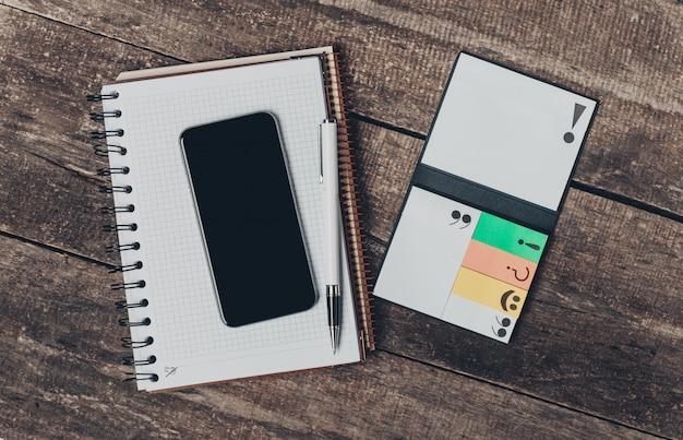 Smartphone con lo schermo nero e il blocco note in bianco aperto sulla fine della tavola su