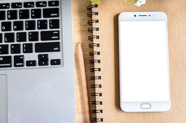 Smartphone con notebook e laptop su un desktop