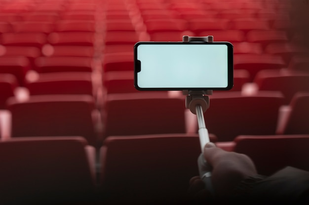 Smartphone con un bastone selfie nelle mani