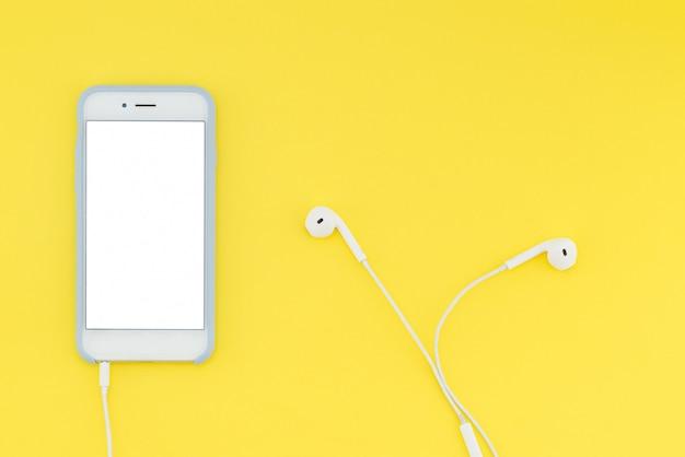 Smartphone con uno schermo bianco con le cuffie su uno sfondo giallo. vista dall'alto. disteso.