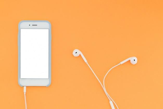 Smartphone con uno schermo bianco e cuffie sullo sfondo arancione. vista dall'alto. disteso.