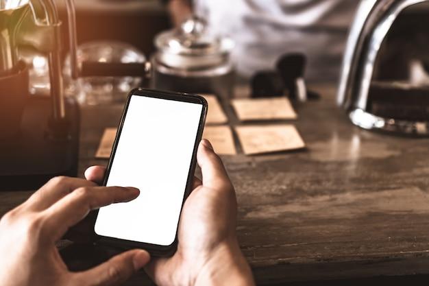 Smartphone della mano della donna per fare affari di lavoro, rete sociale, comunicazione con lo schermo bianco come copyspace.