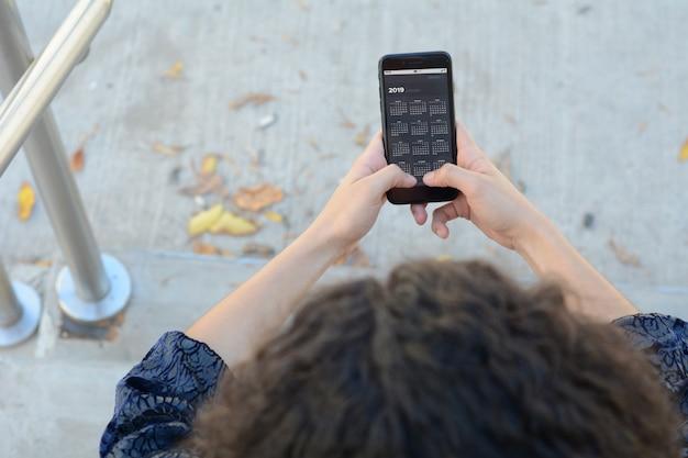 Smartphone della tenuta della donna con l'app del calendario