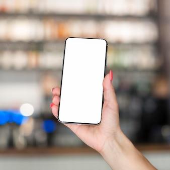 Smartphone della tenuta della donna con lo spazio della copia