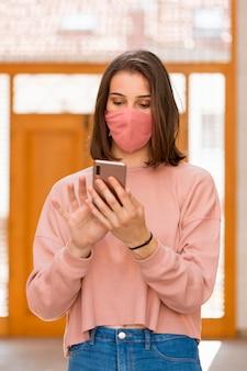 Smartphone della tenuta della donna del colpo medio