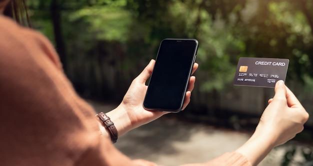 Smartphone della tenuta della donna e carta di credito