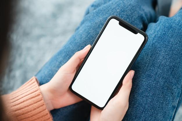 Smartphone della tenuta della mano con uno schermo in bianco