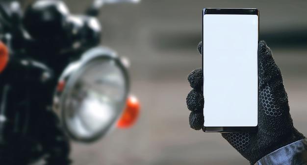 Smartphone della tenuta della mano del motociclista con lo schermo in bianco.
