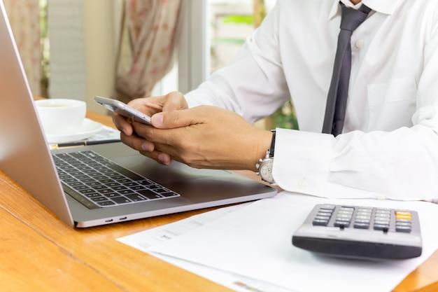 Smartphone della tenuta della mano dell'uomo d'affari con il computer portatile allo scrittorio di legno