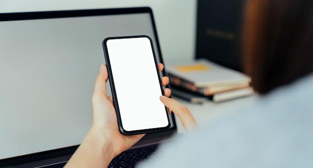 Smartphone della tenuta della mano della donna con lo schermo in bianco dello spazio della copia per la vostra pubblicità. laptop sul tavolo.