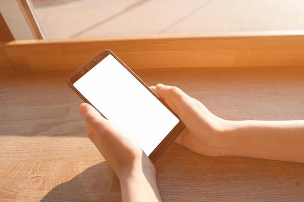Smartphone della tenuta della mano della donna con lo schermo in bianco.