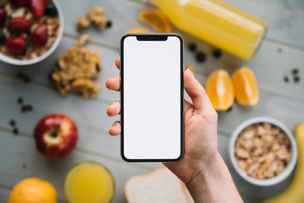 Smartphone della tenuta della persona con lo schermo in bianco sopra la tavola con i frutti