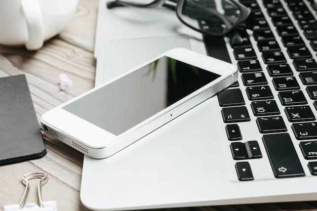 Smartphone dello schermo in bianco per lo spazio della copia e articoli per ufficio su di legno