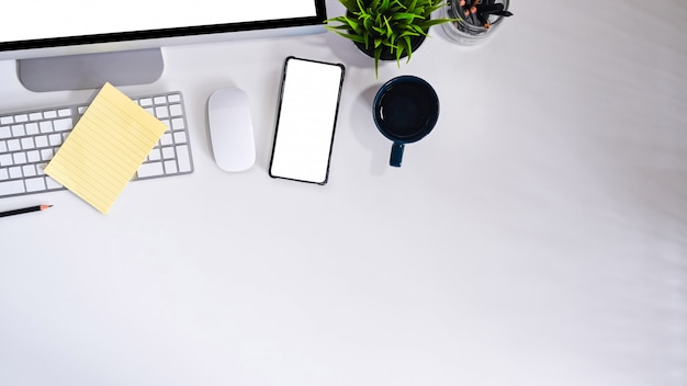 Smartphone dello schermo vuoto del modello sulla tavola di vista superiore della scrivania.