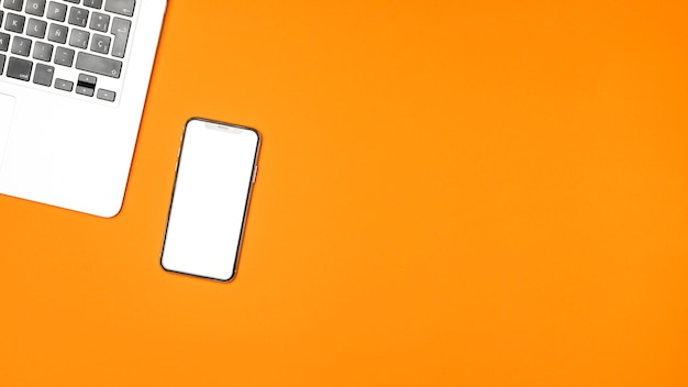 Smartphone di mockup di vista superiore con fondo arancio