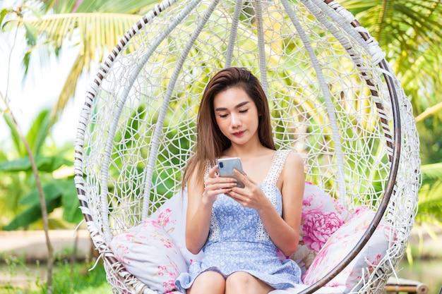 Smartphone di uso di seduta della giovane donna nell'oscillazione bianca