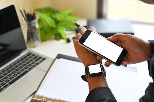 Smartphone e smartwatch sulle mani dell'uomo d'affari, montaggio di mockup una tecnologia mobile.