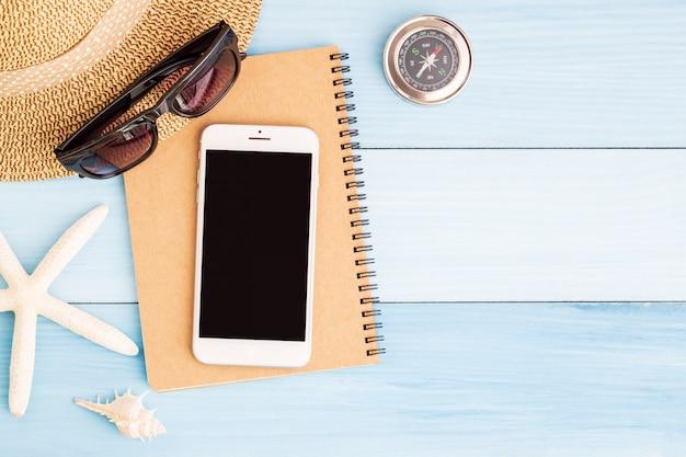 Smartphone e taccuino sulla tavola di legno blu, viaggio di concetto per l'estate