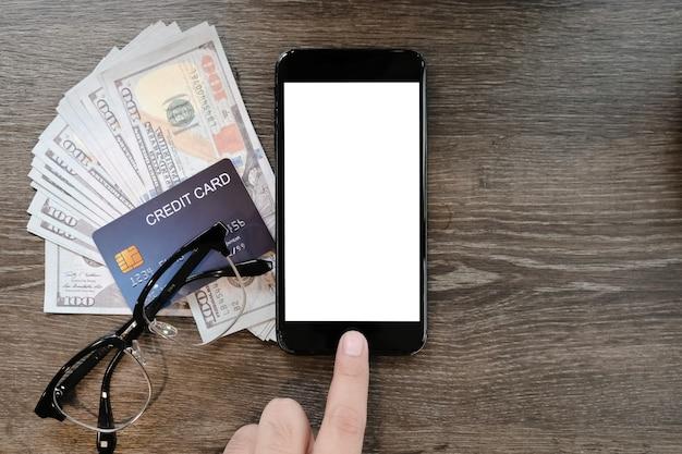 Smartphone in bianco della tenuta della mano della donna con la carta di credito e soldi sulla tavola in caffetteria