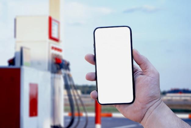 Smartphone in primo piano della mano sullo sfondo di una stazione di servizio. pagamento rifornimento online.