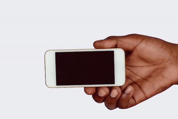 Smartphone maschio della holding della mano con lo schermo in bianco.