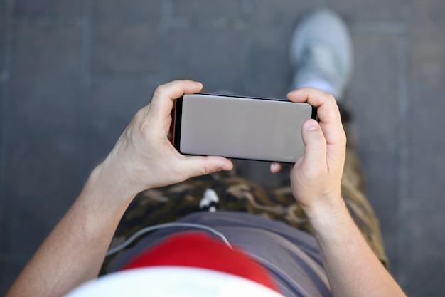 Smartphone maschio della stretta della mano con lo spazio in bianco