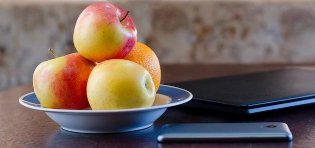 Smartphone, mele su un piatto e un computer portatile. pausa salutare. vista panoramica