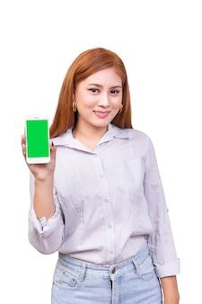 Smartphone mobile della tenuta asiatica della donna con lo schermo verde in bianco, percorso di ritaglio
