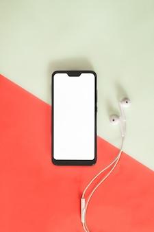 Smartphone moderno con lo schermo bianco e le cuffie sull'arancia e sul verde