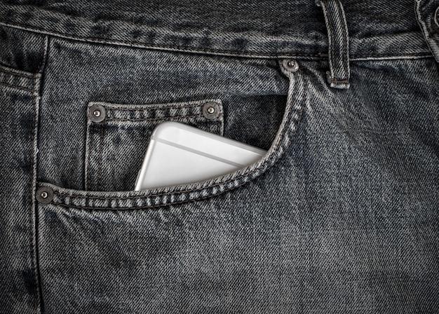 Smartphone nella tasca frontale dei jeans neri