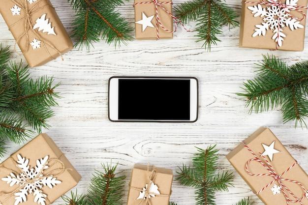 Smartphone nero bianco con schermo isolato, sopra la scrivania in legno con decorazioni natalizie. vista dall'alto