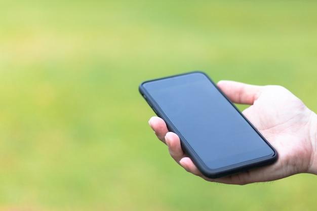 Smartphone nero del primo piano sulle mani di un uomo su fondo verde con lo spazio della copia