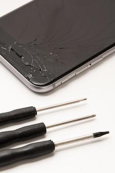 Smartphone rotto e piccoli cacciaviti per la riparazione