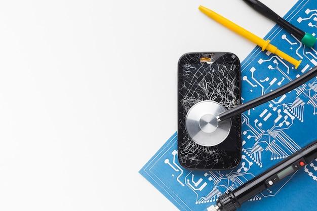 Smartphone rotto vista dall'alto con strumenti di riparazione