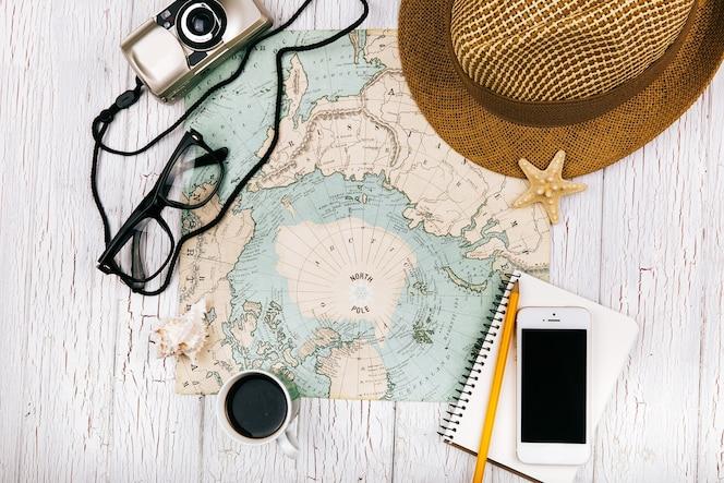 Smartphone si trova su un notebook davanti a una tazza di caffè sulla mappa, cappello, macchina fotografica e occhiali intorno ad esso
