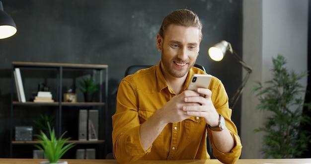 Smartphone sorridente della tenuta del giovane in mani in ufficio.