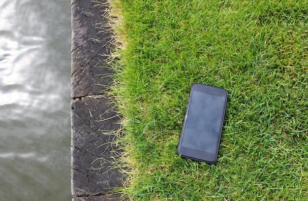 Smartphone su erba verde e piccolo fiume, in riva al lago