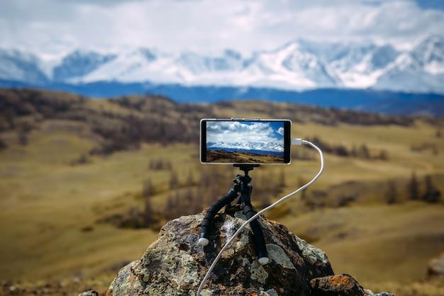 Smartphone su treppiede montato su pietra di fronte a una vista mozzafiato sulle cime innevate.