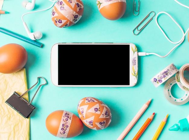 Smartphone tra set di uova di gallina marrone e articoli di cancelleria