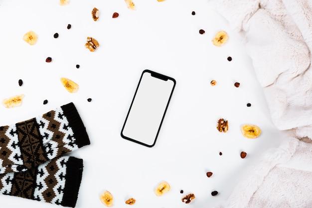 Smartphone vicino a noci e vestiti
