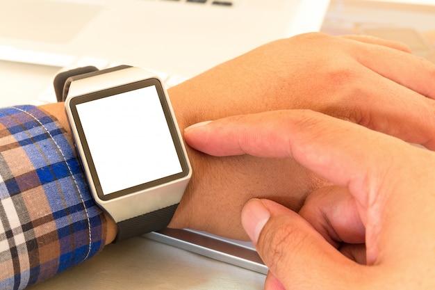 Smartwatch delle mani dell'uomo d'affari con con lo schermo in bianco.